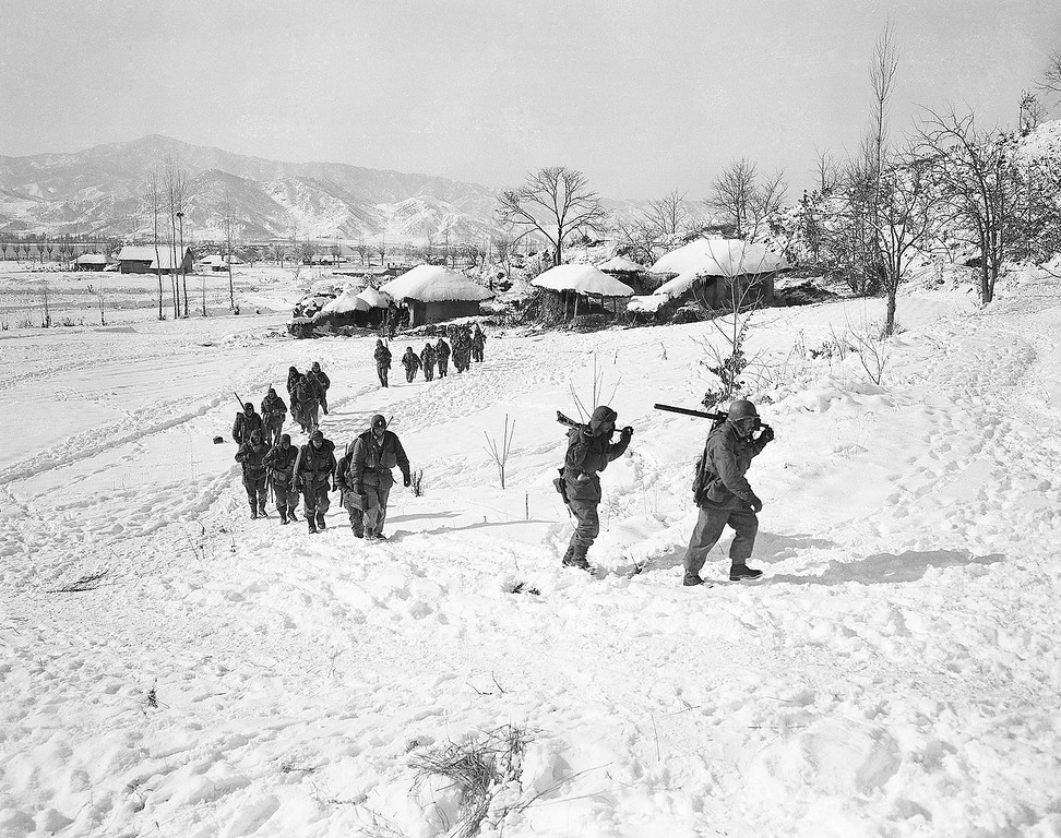 . Well-armed infantrymen move up hill in Wonju front sector, South Korea on Jan. 13, 1951 as Allied forces launch attack against enemy held hill in sub-zero temperatures. (AP Photo/James Martenhoff)