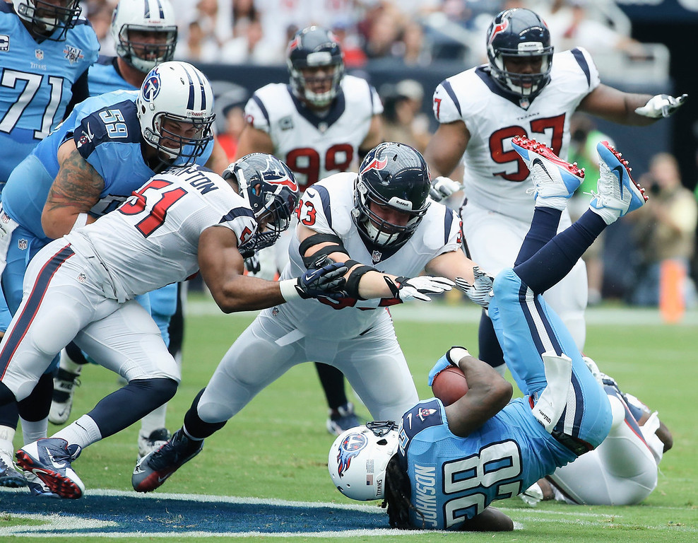 . Chris Johnson #28 of the Tennessee Titans is tackled by a group of  Houston Texans at Reliant Stadium on September 15, 2013 in Houston, Texas.  (Photo by Scott Halleran/Getty Images)