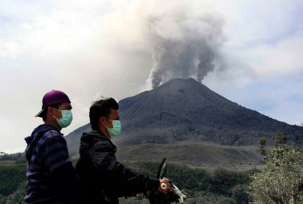 . Indonesian villagers ride on a motorbike as Mount Sinabung spews volcanic ash as seen from Naman Teran village, Karo, North Sumatra, Indonesia, 26 November 2013.   EPA/DEDI SAHPUTRA