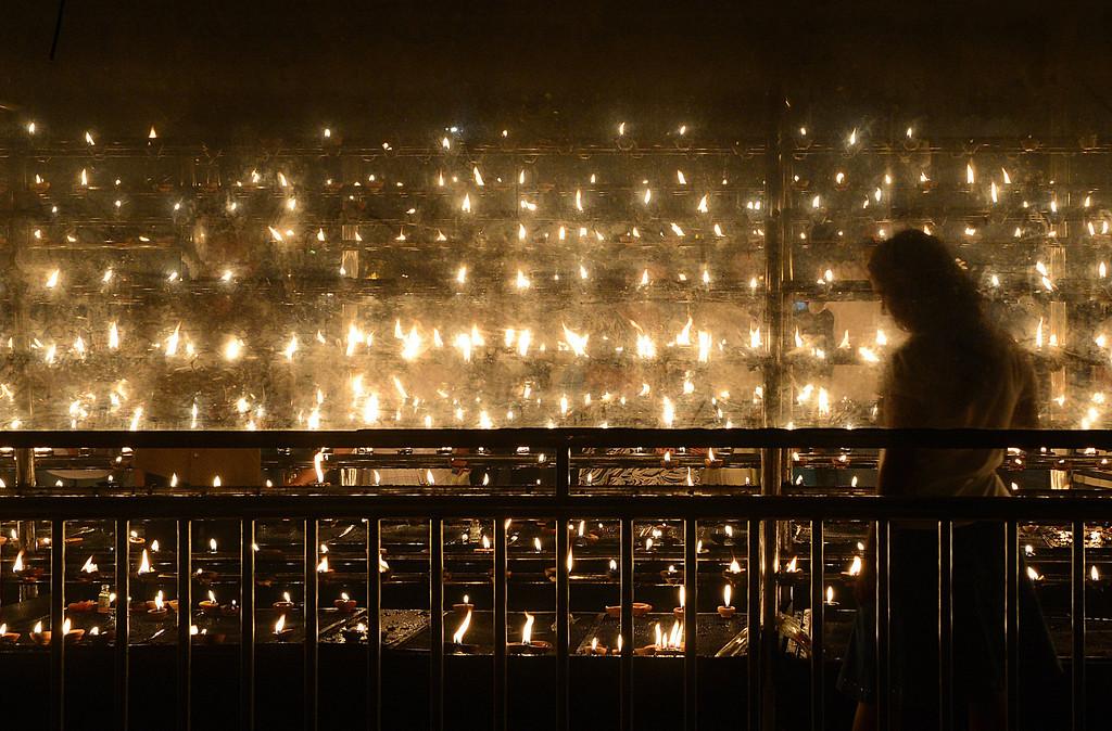 . A Sri Lankan Buddhist devotee lights oil lamps at the Kelaniya Temple in Kelaniya on January 1, 2013. Many Sri Lankans marked the beginning of the 2013 New Year with religious ceremonies.  Ishara S.KODIKARA/AFP/Getty Images