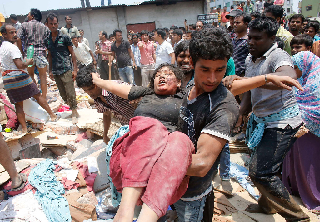 . People rescue a garment worker who was trapped under the rubble of the collapsed Rana Plaza building in Savar, 30 km (19 miles) outside Dhaka April 24, 2013. REUTERS/Andrew Biraj