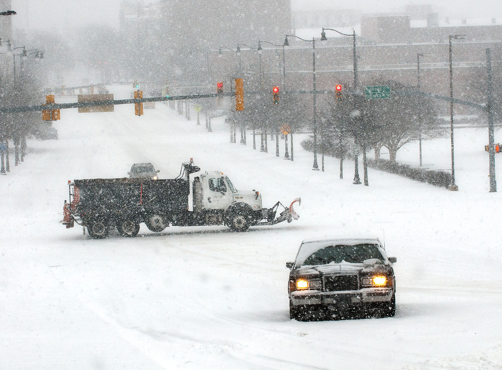 . A car stuck is in middle of the snow covered road on Hay Street as a snow plow passes in the background during a winter storm Wednesday, Feb. 12, 2014, in Fayetteville, N.C.  (AP Photo/The Fayetteville Observer, Cindy Burnham )