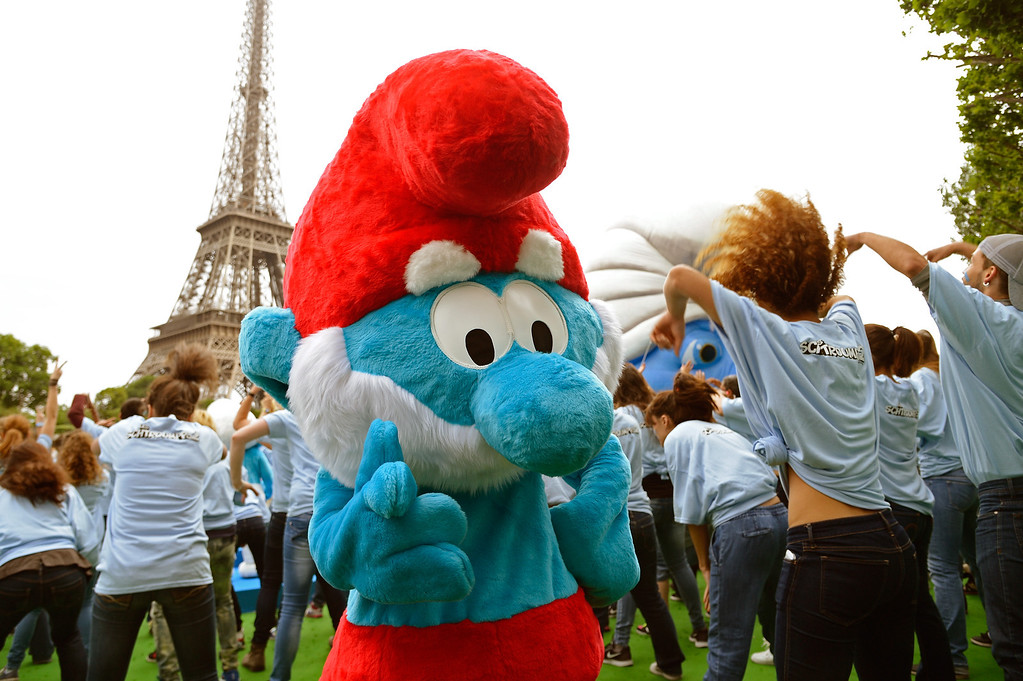 """. A performer dressed as the Smurf character \""""Papa Smurf\"""" takes part to a dance with performers as part of Global Smurfs Day celebrations on June 22, 2013 on the Seine river bank in Paris, France.  (Photo by Pascal Le Segretain/Getty Images for Sony Pictures Entertainment)"""