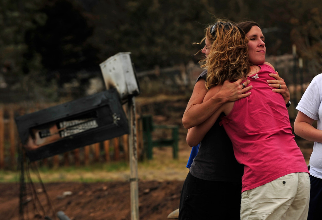 . Neighbors Kate Stefani, right, in pink, and Melissa Mgana, embrace. Both lost their homes in the Waldo Canyon Fire. Residents were allowed back on July 1, 2012 into the Mountain Shadows subdivision to visit their homes five days after the Waldo Canyon fire ravaged their neighborhood. Helen H. Richardson, The Denver Post