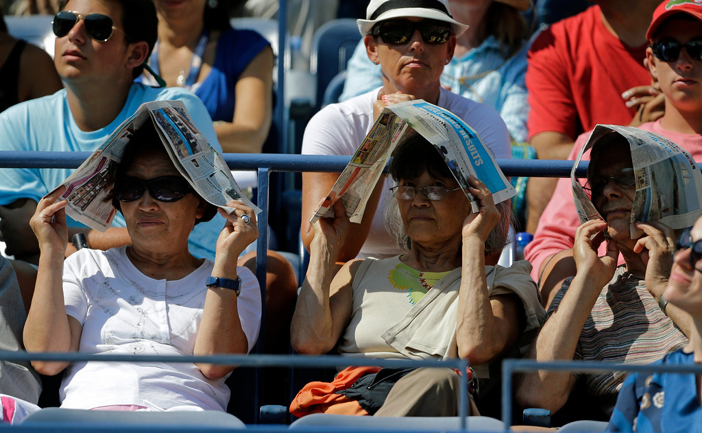. Fans shade themselves from the sun while watching a first round match at the 2013 U.S. Open tennis tournament Tuesday, Aug. 27, 2013, in New York. (AP Photo/Mike Groll)