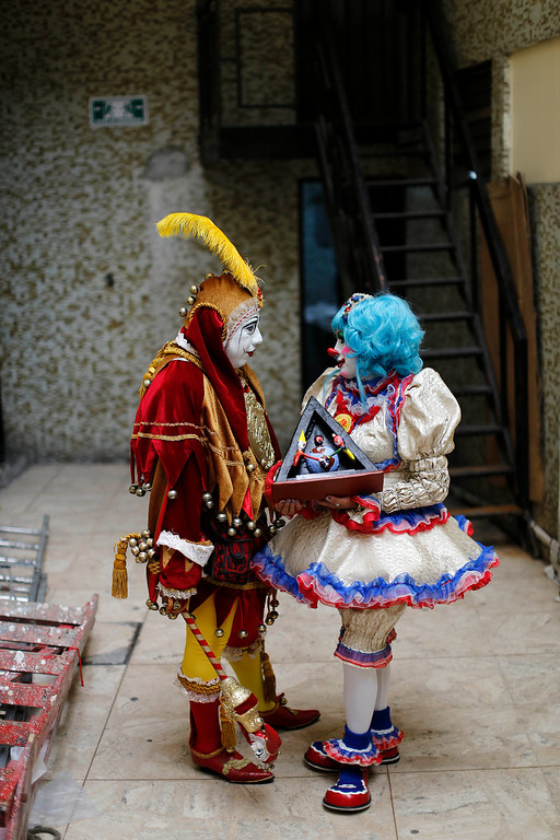 . A pair of clowns talk backstage prior to giving a special award to a clown on the second day of the 17th International Clown Convention at a theater in Mexico City, Tuesday, Oct. 22, 2013. Despite their elaborate face paint, weird wigs and rubber noses of different sizes, the clowns reveal a slice of the humanity they seek to entertain: happy and sad, pensive and exuberant, playful and macabre. (AP Photo/Dario Lopez-Mills)