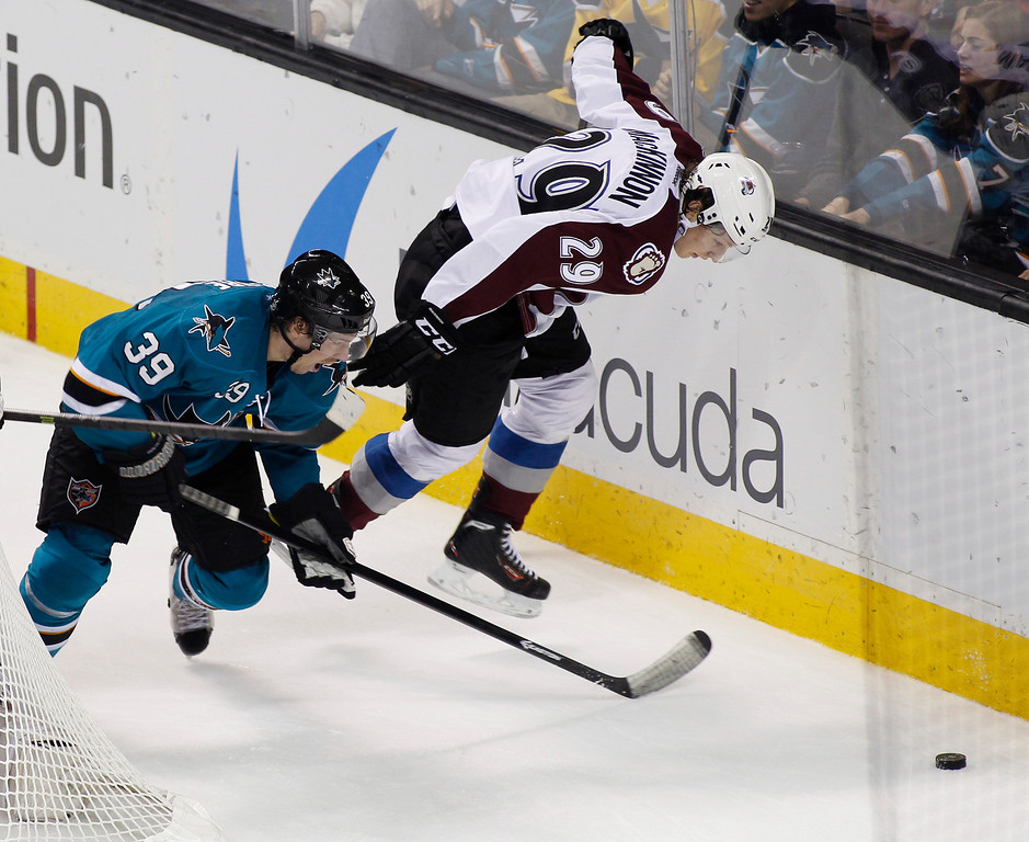 . San Jose Sharks\' Logan Couture, left, and Colorado Avalanche\'s Nathan MacKinnon struggle for the puck during the second period of an NHL hockey game, Monday, Dec. 23, 2013, in San Jose, Calif. (AP Photo/George Nikitin)