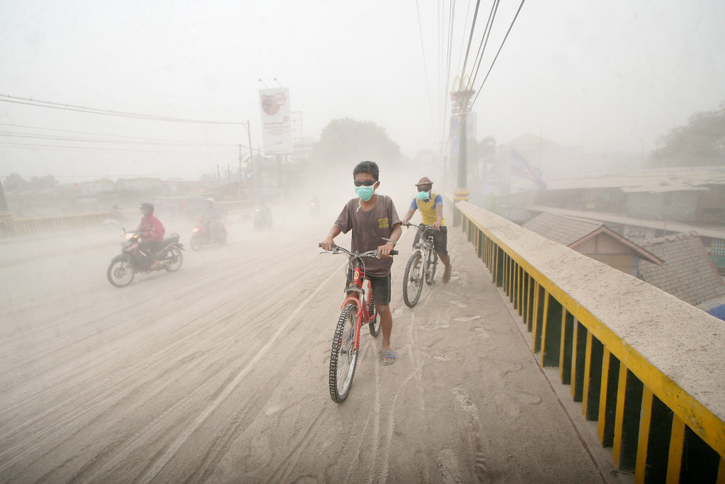 . Indonesian residents ride their bikes on a street covered with ash from the Mount Kelud volcano in Yogyakarta, Indonesia, 14 February 2014.  EPA/BIMO SATRIO
