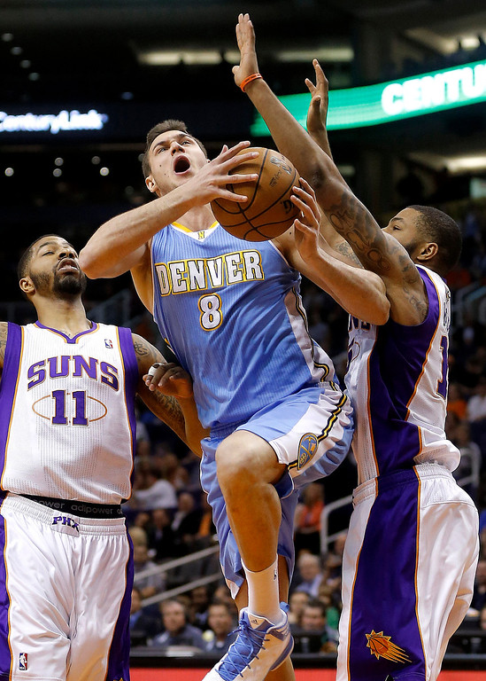 . Denver Nuggets\' Danilo Gallinari (8), of Italy, drives between Phoenix Suns\' Markieff Morris (11) and Marcus Morris, right, during the first half of an NBA basketball game, Monday, March 11, 2013, in Phoenix. (AP Photo/Matt York)
