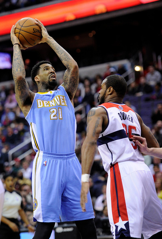 . Denver Nuggets guard Wilson Chandler (21) looks to the basket against Washington Wizards forward Trevor Booker (35) during the first half of an NBA basketball game, Friday, Feb. 22, 2013, in Washington. The Wizards won 119-113. (AP Photo/Nick Wass)