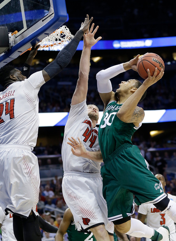 . Manhattan forward Ashton Pankey (30) shoots as Louisville forward Montrezl Harrell (24) and forward Stephan Van Treese (44) defend during the first half in a second-round game in the NCAA college basketball tournament Thursday, March 20, 2014, in Orlando, Fla. (AP Photo/John Raoux)