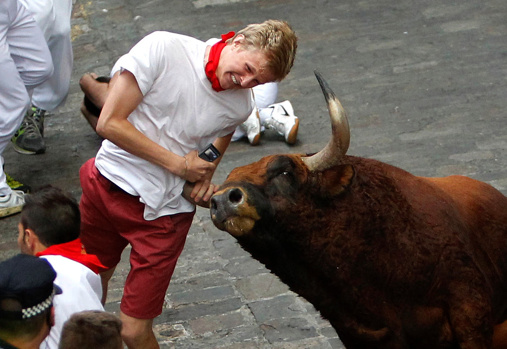 """. A runner is gored by an \""""El Pilar\"""" fighting bull during the running of the bulls at the San Fermin festival, in Pamplona, Spain, Friday, July 12, 2013. An American and two Spaniards were gored Friday during a danger-filled sixth bull run of Spainís San Fermin festival, with one loose bull causing panic in the packed streets of Pamplona city.  (AP Photo)"""