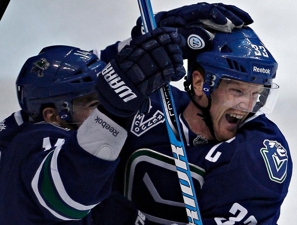 . Vancouver Canucks Henrik Sedin (R) and teammate Alex Burrows celebrate a goal scored against the Colorado Avalanche by Daniel Sedin during the third period of their NHL hockey game in Vancouver, British Columbia March 28, 2013.   REUTERS/Andy Clark