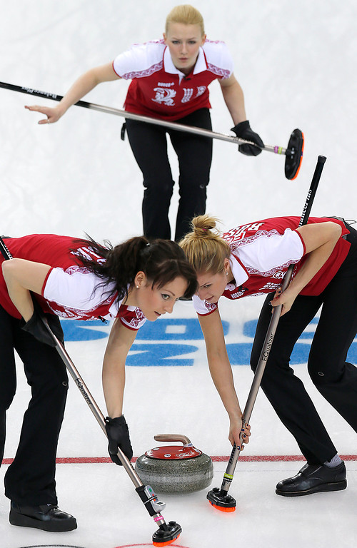 . Russia\'s Alexandra Saitova, top, watches as Ekaterina Galkina, left, and Margarita Fomina, right, sweep the ice during the women\'s curling competition against South Korea at the 2014 Winter Olympics, Thursday, Feb. 13, 2014, in Sochi, Russia. (AP Photo/Wong Maye-E)