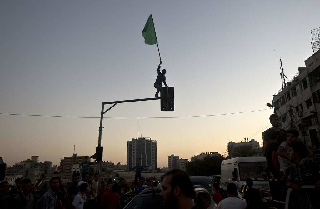 ". A Palestinian plants a Hamas flag atop a street light as people gather in the streets of Gaza City on August 26, 2014, to celebrate the long-term truce agreed between Israel and the Palestinians. Israel has agreed to observe an ""unlimited\"" ceasefire in the Gaza Strip, a senior official told AFP on Tuesday, shortly after the deal was announced by the Palestinians. MAHMUD HAMS/AFP/Getty Images"