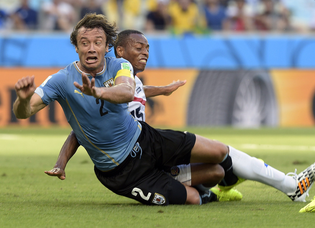 . Costa Rica\'s defender Junior Diaz (R) tackles Uruguay\'s defender Diego Lugano during a Group D football match between Uruguay and Costa Rica at the Castelao Stadium in Fortaleza during the 2014 FIFA World Cup on June 14, 2014. AFP PHOTO / DANIEL GARCIA