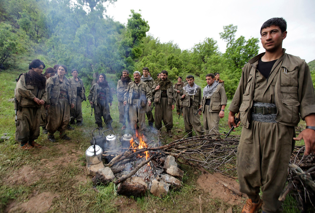 . Kurdistan Workers Party (PKK) fighters rest around a fire in northern Iraq May 14, 2013. The first group of Kurdish militants to withdraw from Turkey under a peace process entered northern Iraq on Tuesday, and were greeted by comrades from the Kurdistan Workers Party (PKK), in a symbolic step towards ending a three-decades-old insurgency. The 13 men and women, carrying guns and with rucksacks on their backs, arrived in the area of Heror, near Metina mountain on the Turkish-Iraqi border, a Reuters witness said. REUTERS/Azad Lashkari