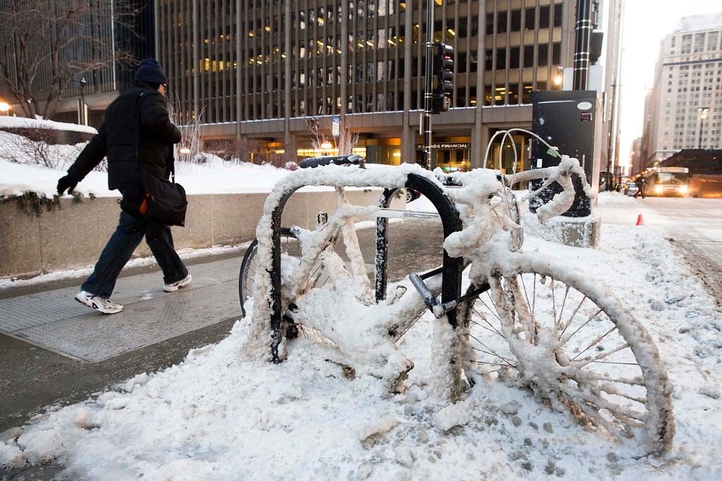 . A man walks past a snow encrusted bicycle with wind chills nearing minus 30 Fahrenheit on Tuesday, Jan. 7, 2014, in downtown Chicago.  Dangerously cold polar air snapped decades-old records as it spread Tuesday from the Midwest to southern and eastern parts of the U.S. and eastern Canada, making it hazardous to venture outside and keeping many schools and businesses closed. (AP Photo/Andrew A. Nelles)