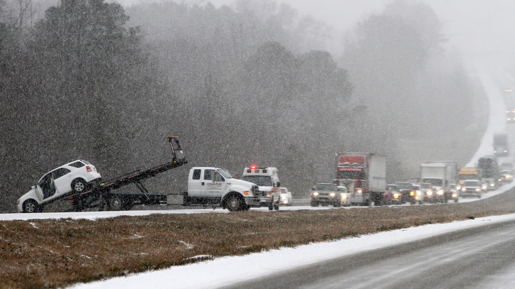 . Traffic backs up as a wrecker pulls a car out of a ditch on I-65 during an unual snow Tuesday, Jan. 28, 2014, in Clanton, Ala.   A rare storm left a slippery layer of ice and snow across a region unaccustomed to dealing with the wintry threat. (AP Photo/Butch Dill)