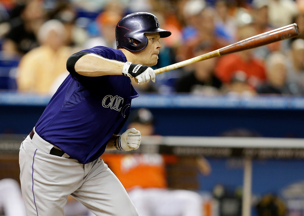 . Colorado Rockies\' Justin Morneau hits a single in the fourth inning of an opening day baseball game against the Miami Marlins, Monday, March 31, 2014, in Miami. (AP Photo/Lynne Sladky)