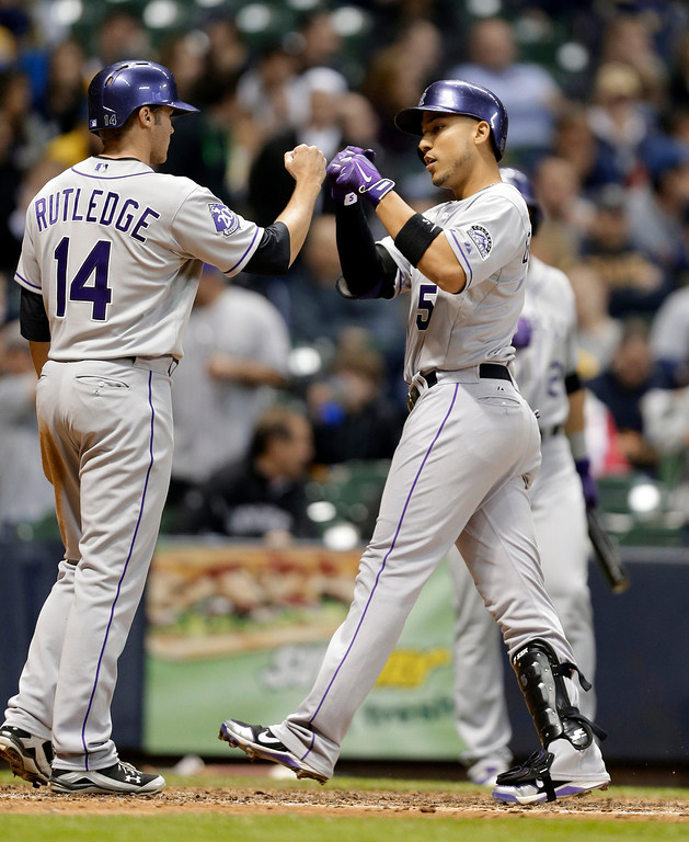 . Colorado Rockies\' Carlos Gonzalez (5) gets a fist-bump from Josh Rutledge after Gonzalez\'s two-run home run against the Milwaukee Brewers during the fifth inning of a baseball game Tuesday, April 2, 2013, in Milwaukee. (AP Photo/Jeffrey Phelps)