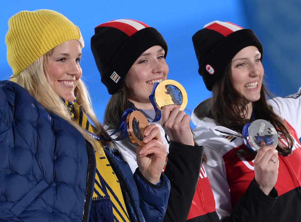 . Canada\'s silver medallist Kelsey Serwa (R), Canada\'s gold medallist Marielle Thompson (C) and Sweden bronze medallist Anna Holmlund pose during the Women\'s Freestyle Skiing Ski Cross Medal Ceremony at the Sochi medals plaza during the Sochi Winter Olympics on February 21, 2014.  AFP PHOTO / ANDREJ  ISAKOVIC/AFP/Getty Images