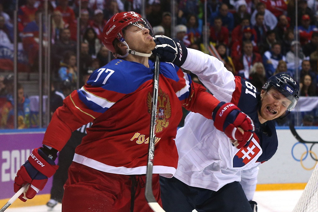 . Milan Bartovic #61 of Slovakia comes into contact with Anton Belov #77 of Russia during the Men\'s Ice Hockey Preliminary Round Group A game on day nine of the Sochi 2014 Winter Olympics at Bolshoy Ice Dome on February 16, 2014 in Sochi, Russia.  (Photo by Bruce Bennett/Getty Images)