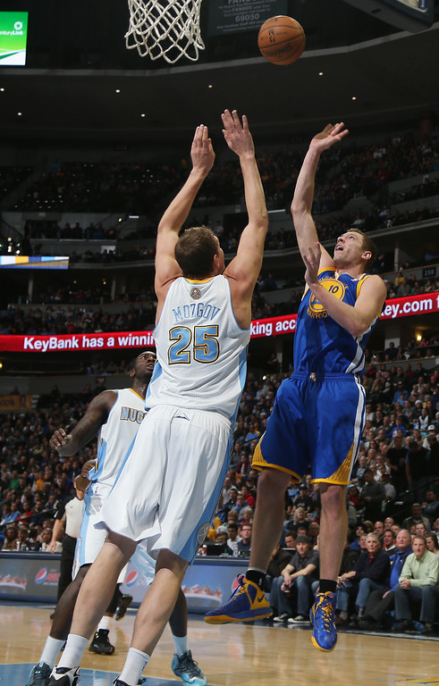 . Golden State Warriors forward David Lee, right, lobs a shot for a basket over Denver Nuggets center Timofey Mozgov, of Russia, in the first quarter of an NBA basketball game in Denver, Monday, Dec. 23, 2013. (AP Photo/David Zalubowski)
