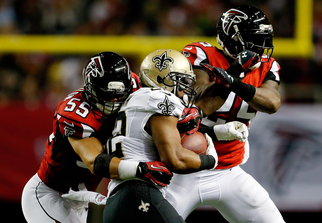 . Running back Mark Ingram #22 of the New Orleans Saints carries the ball as outside linebacker Paul Worrilow #55 and strong safety William Moore #25 of the Atlanta Falcons defend during a game at the Georgia Dome on November 21, 2013 in Atlanta, Georgia.  (Photo by Kevin C. Cox/Getty Images)