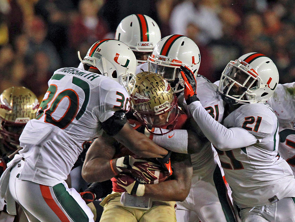 . Miami\'s defense smoothers Florida State\'s Karlos Williams in the first quarter of an NCAA college football game Saturday, Nov. 2, 2013, in Tallahassee, Fla. (AP Photo/Miami Herald, Charles Trainor Jr.)