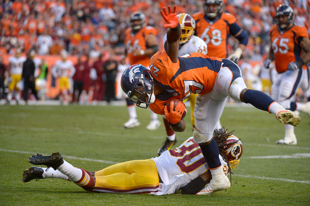 . Denver Broncos running back Knowshon Moreno (27) breaks a tackle by Washington Redskins cornerback E.J. Biggers (30) during a run that set up a field goal in the /third quarter.   (Photo by Tim Rasmussen/The Denver Post)