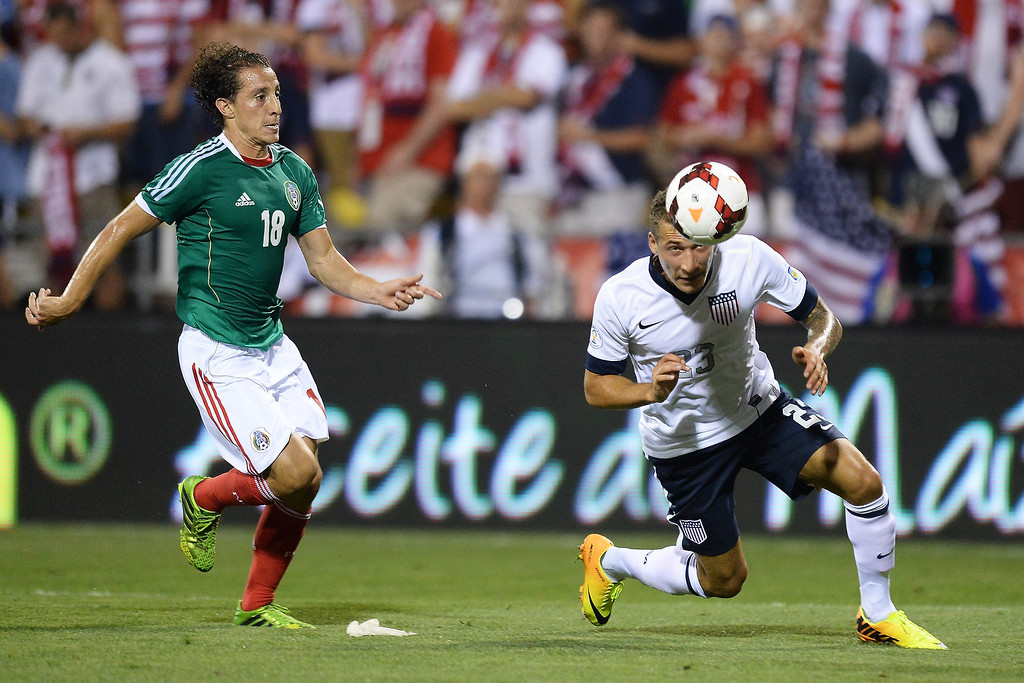 . Fabian Johnson #23 of the United States Men\'s National Team heads the ball away from Andres Guardado #18 of the Mexico Men\'s National Team in the first half at Columbus Crew Stadium on September 10, 2013 in Columbus, Ohio.  (Photo by Jamie Sabau/Getty Images)