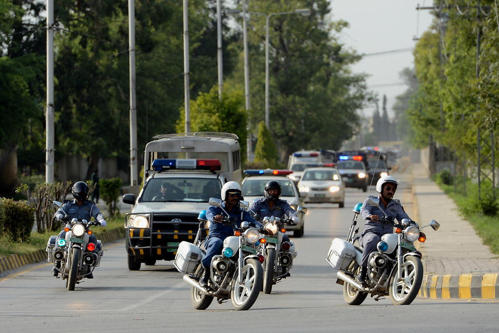 . Pakistani police lead ambulances carrying the coffins of foreign tourists as they come out from Chaklala air base in Rawalpindi on June 23, 2013. FAROOQ NAEEM/AFP/Getty Images