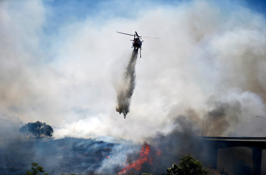 . A helicopter attacks a wild fire burning  Tuesday, May 13, 2014, in San Diego. Wildfires forced the evacuation of 20,000 people as a high-pressure system brought unseasonable heat and gusty winds to a parched state that should be in the middle of its rainy season. (AP Photo)