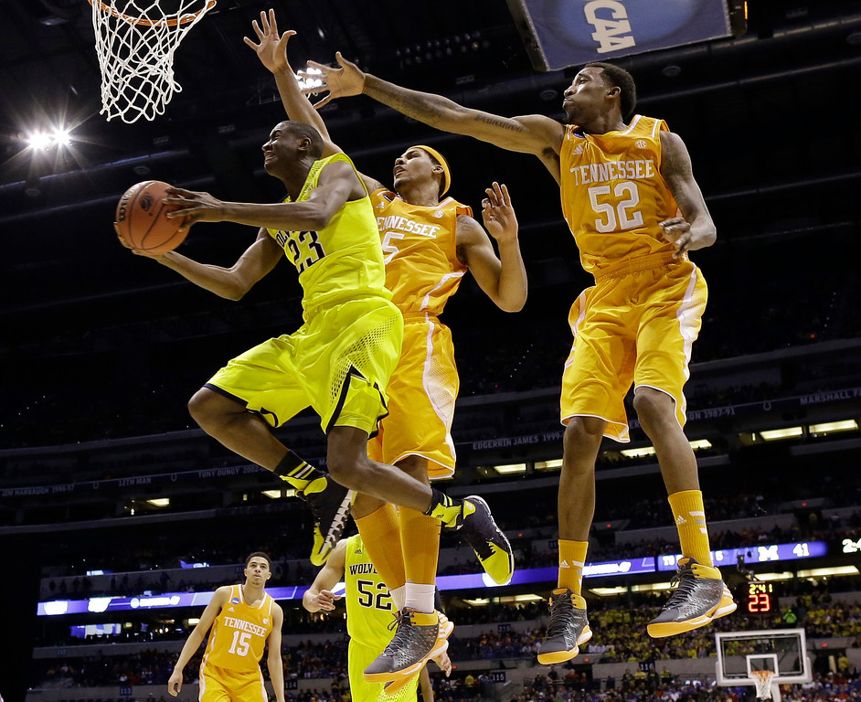 . Michigan\'s Caris LeVert (23) shoots past Tennessee\'s Jarnell Stokes (5) and Jordan McRae (52) during the first half of an NCAA Midwest Regional semifinal college basketball tournament game Friday, March 28, 2014, in Indianapolis. (AP Photo/David J. Phillip)