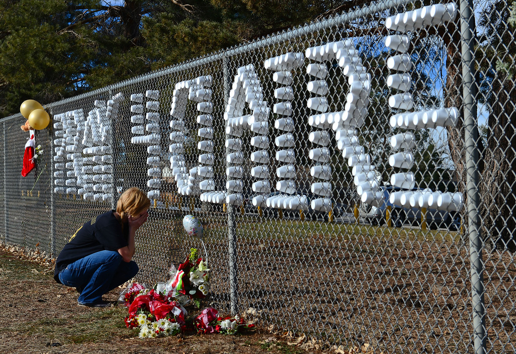 . Kristen Wallace, 17, a takes a moment to pray at a tribute set up for shooting victim Claire Davis along Dry Creek road near Arapahoe High School in Centennial, CO on December 15, 2013. Students from the high school attended a prayer service to pray for the recovery of Davis who was shot during the recent shooting at the high school.  (Photo By Helen H. Richardson/ The Denver Post)