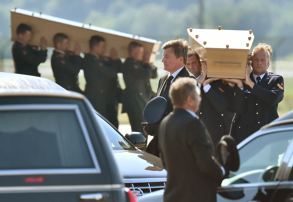 . Dutch military men carry coffins containing the bodies of victims of downed Malaysia Airlines flight MH17, during a ceremony at Eindhoven Airbase on July 23, 2014, after a Hercules transport plane carrying the coffins landed from Ukraine. The first bodies from flight MH17 arrived in the Netherlands on July 23 almost a week after it was shot down over Ukraine, with grieving relatives and the king and queen of The Netherlands solemnly receiving the as yet unidentified victims. AFP PHOTO / JOHN THYS/AFP/Getty Images