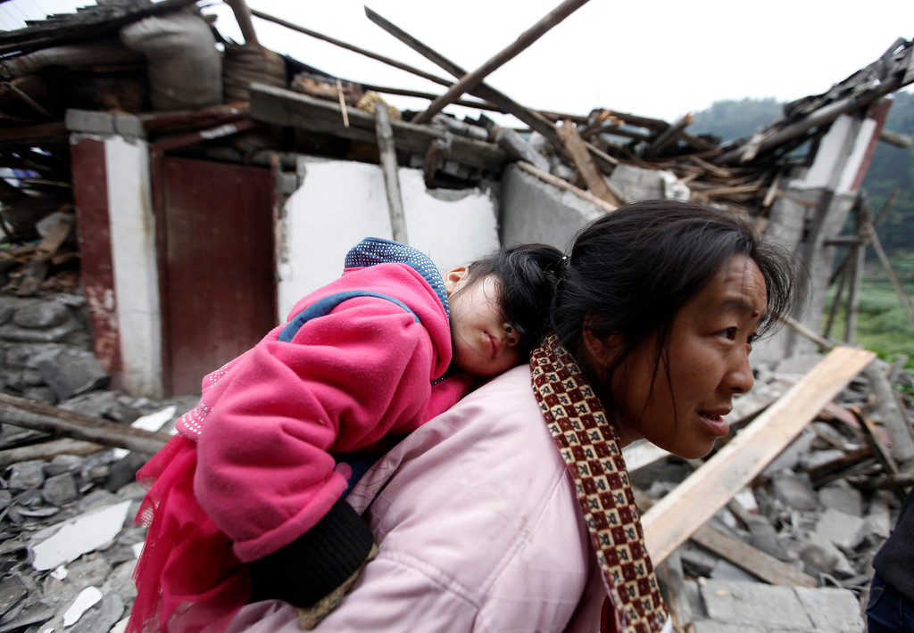 . A survivor carries her sleeping daughter as she walks past debris at a village up on the mountainside after Saturday\'s earthquake hit Lingguan township, in Baoxing county in Ya\'an, Sichuan province April 22, 2013. REUTERS/Jason Lee