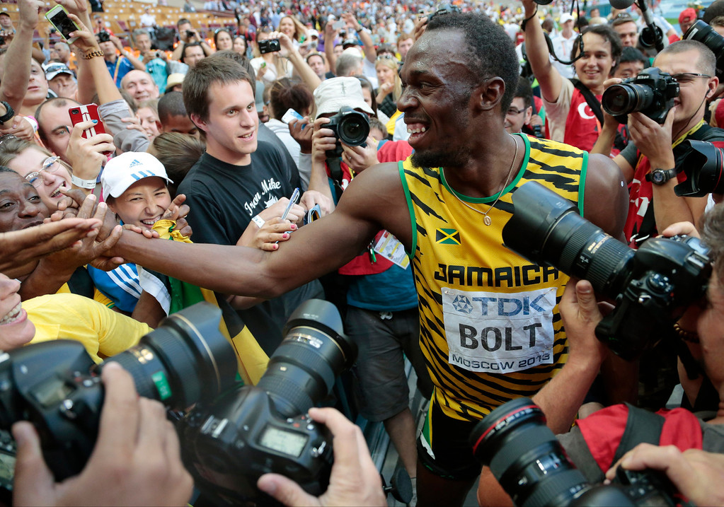 . Jamaica\'s Usain Bolt is surrounded spectators and photographers as he celebrates winning gold in the men\'s 200-meter final at the World Athletics Championships in the Luzhniki stadium in Moscow, Russia, Saturday, Aug. 17, 2013. (AP Photo/Ivan Sekretarev)