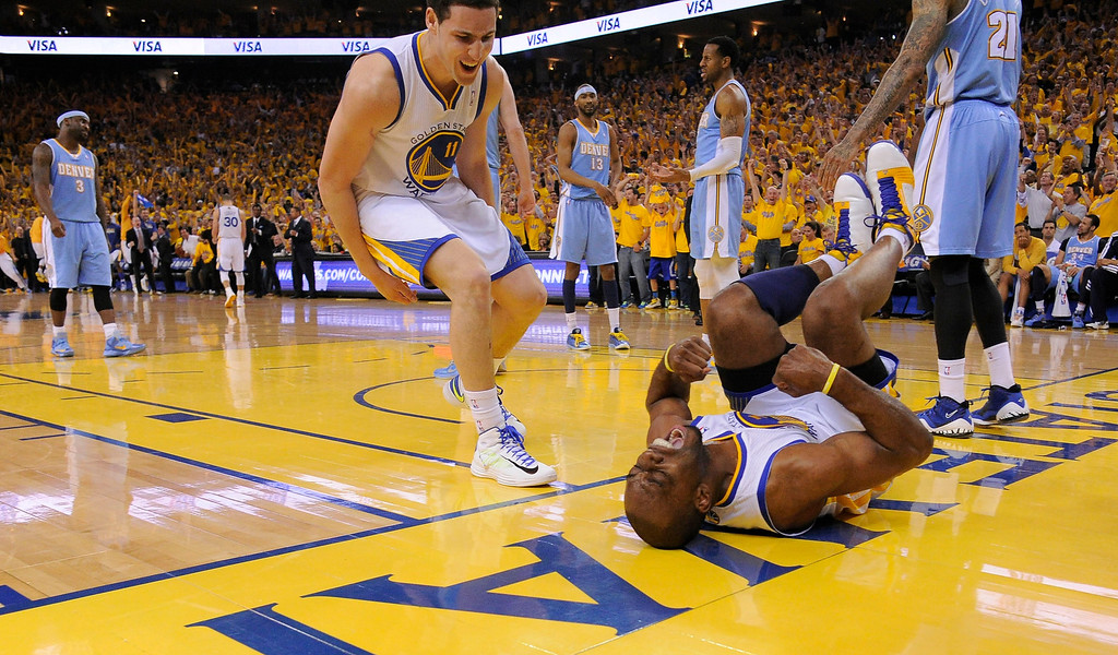 . Carl Landry (7) of the Golden State Warriors jubilates laying on the court after getting fouled during the third quarter as teammate Klay Thompson (11) of the Golden State Warriors comes over to help him up in Game 6 of the first round NBA Playoffs May 2, 2013 at Oracle Arena. (Photo By John Leyba/The Denver Post)