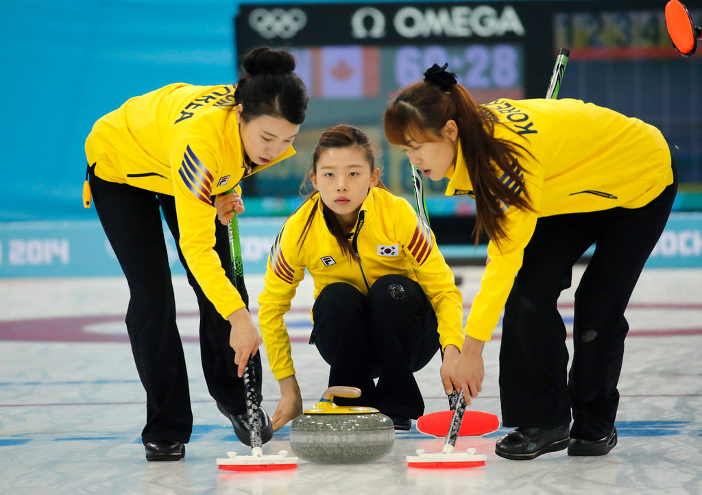 . South Korea\'s Lee Seulbee (C) delivers a stone while Um Min Ji (L) and Gim Un Chi sweep during the Round Robin match between South Korea and Canada of the Women\'s Curling competition in the Ice Cube Curling Center at the Sochi 2014 Olympic Games, Sochi, Russia.  EPA/ANATOLY MALTSEV
