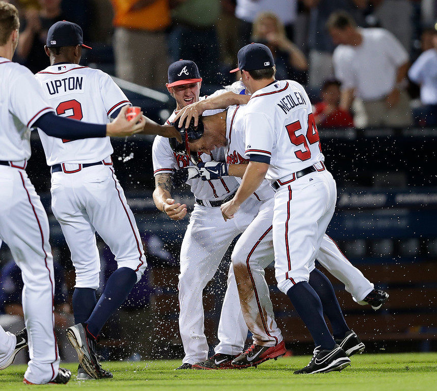 . Atlanta Braves shortstop Andrelton Simmons, second from right, is mobbed by teammates Kris Medlen, right, and Jordan Schafer (17) after driving in the game-winning run with a triple in the 10th inning of a baseball game against the Colorado Rockies in Atlanta, Monday, July 29, 2013. Atlanta won 9-8. (AP Photo/John Bazemore)