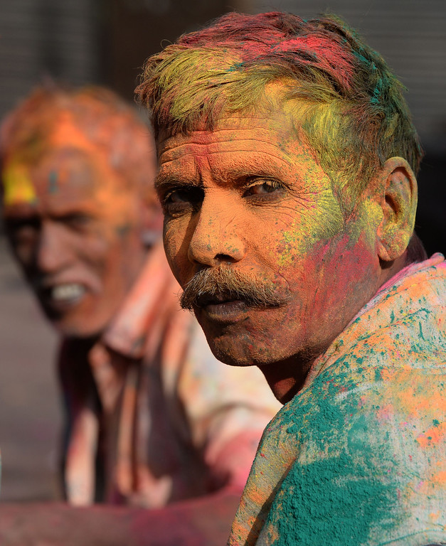 . Indian revelers their faces covered in colored powder, pose as they celebrate Holi, the Festival of Colors in the old quarters of New Delhi on March 17,2014.  Holi, The Festival of Colors, is a popular Hindu spring festival observed in India at the end of the winter season on the last full moon day of the lunar month.   AFP PHOTO /SAJJAD HUSSAIN/AFP/Getty Images