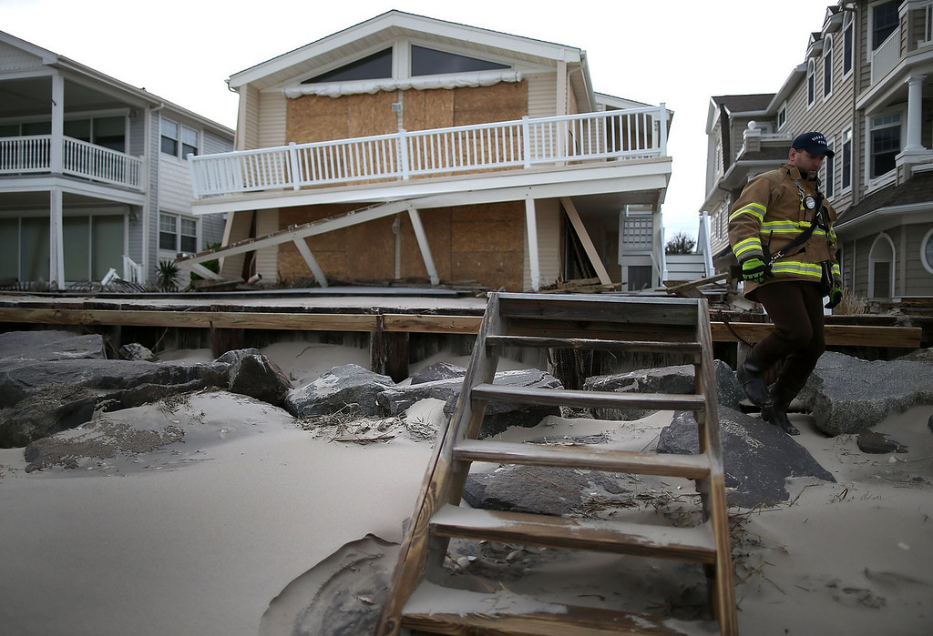 . Firefighter Chris Vliet walks away from a beach front home damaged by Hurricane Sandy on October 30, 2012 in Ocean City, New Jersey. Sandy made landfall last night on the New Jersey coastline bringing heavy winds and record floodwaters. At least two dozen people were reported killed in the United States as millions of people in the eastern United States are experiencing widespread power outages, flooded homes and downed trees. (Photo by Mark Wilson/Getty Images)