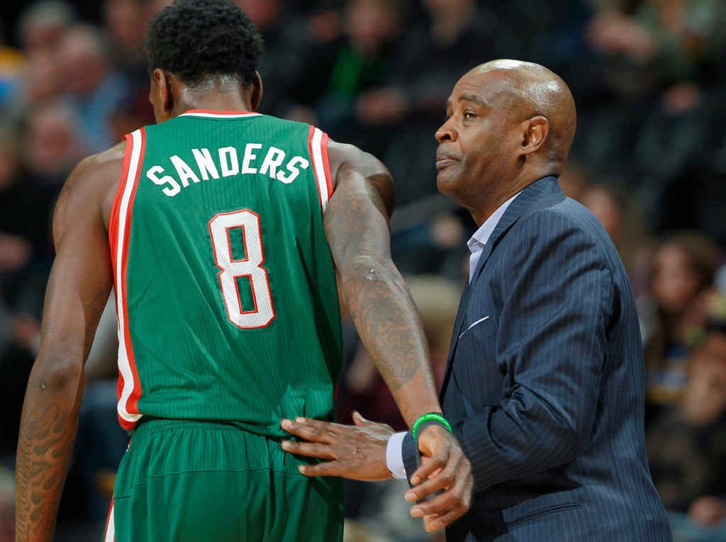 . Milwaukee Bucks head coach Larry Drew, right, confers with center Larry Sanders during a timeout against the Denver Nuggets in the first quarter of an NBA basketball game in Denver, Wednesday, Feb. 5, 2014. (AP Photo/David Zalubowski)