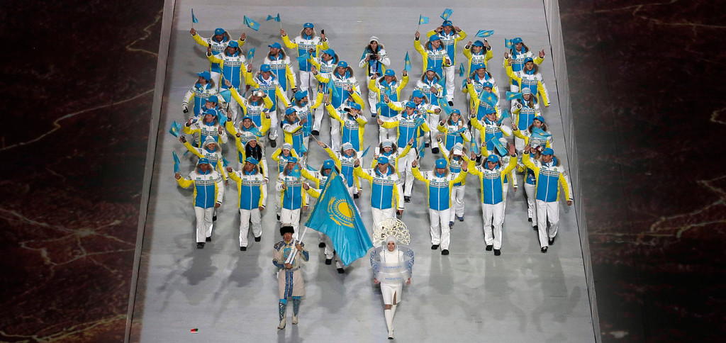 . Yerdos Akhmadiyev of Kazakhstan holds the national flag and enters the arena with his teammates during the opening ceremony of the 2014 Winter Olympics in Sochi, Russia, Friday, Feb. 7, 2014. (AP Photo/Charlie Riedel)