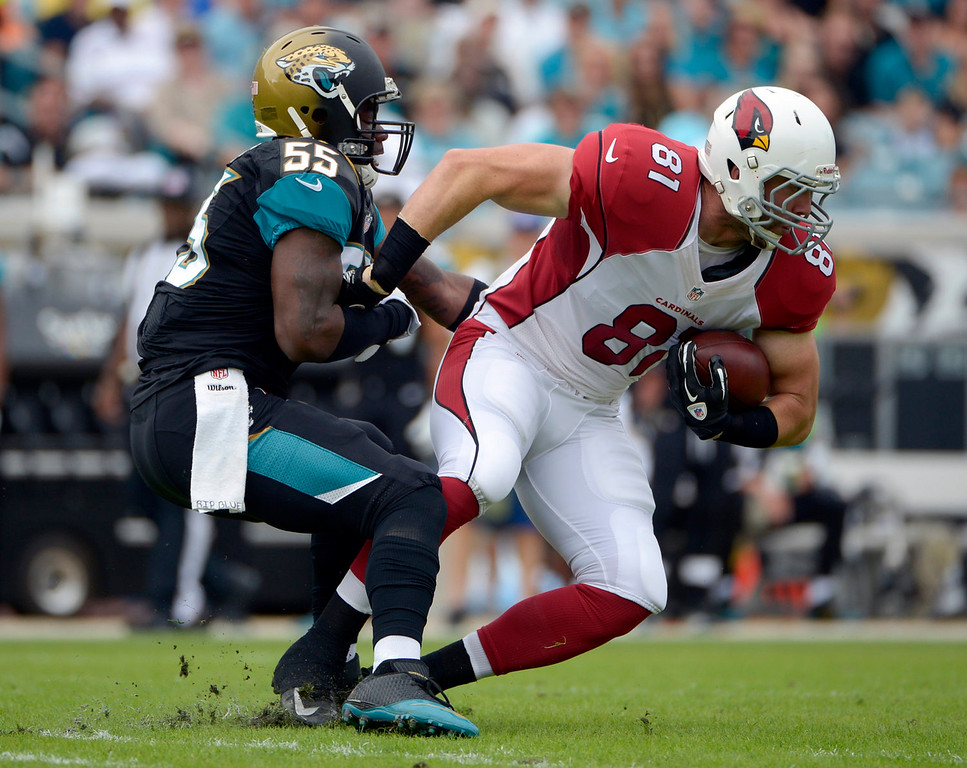 . Arizona Cardinals tight end Jim Dray (81) is tackled by Jacksonville Jaguars outside linebacker Geno Hayes (55) after a reception during the first half of an NFL football game in Jacksonville, Fla., Sunday, Nov. 17, 2013. (AP Photo/Phelan M. Ebenhack)