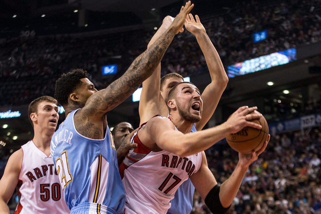. Toronto Raptors\' Jonas Valanciunas, right, grabs a rebound in front of Denver Nuggets\' Wilson Chandler, left, and Timofey Mozgov during the first half of an NBA basketball game on Sunday, Dec. 1, 2013, in Toronto. (AP Photo/The Canadian Press, Chris Young)
