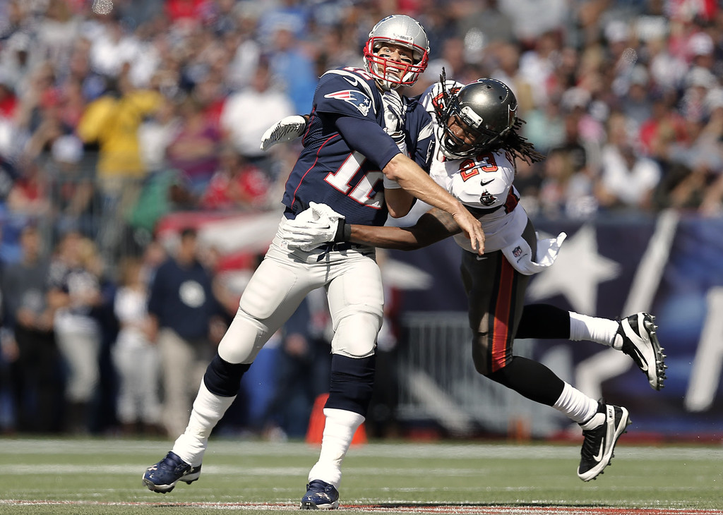 . Quarterback Tom Brady #12 of the New England Patriots gets off a pass as Mark Barron #23 of the Tampa Bay Buccaneers flies into him  during the first half at Gillette Stadium on September 22, 2013 in Foxboro, Massachusetts.  (Photo by Winslow Townson/Getty Images)