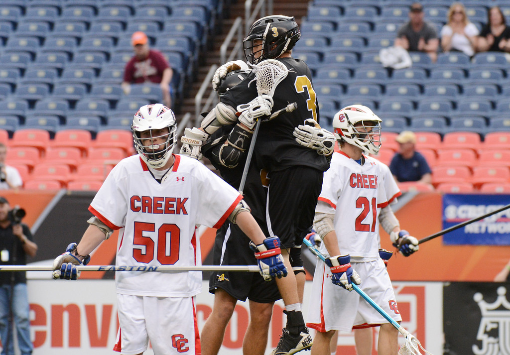 . DENVER, CO. - MAY 18 : Michael Babb (2) and Luc Crabtree (3) of Arapahoe High School celebrate Babb\'s goal between Ben Kingdom (50) and Hunter Burton (21) of Cherry Creek High School during 5A Boy\'s Lacrosse Championship game at Sports Authority Field at Mile High Stadium. Denver, Colorado. May 18, 2013. Arapahoe won 10-7. (Photo By Hyoung Chang/The Denver Post)